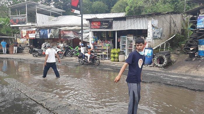 Warga Jalan Curug Nangka memprotes jalan rusak dengan menebar 25kg ikan lele di kubangan jalan di Jalan Curug Nangka, Tamansari, Bogor.
