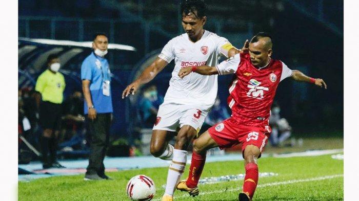 Kapten tim PSM Makasssar, Zulkifli Syukur (kiri) sukses menjaga pergerakan sayap Persija Jakarta Riko Simanjuntak pada laga babak penyisihan grup B