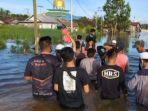 anggota-front-persaudaran-islam-memberikan-bantuan-kepada-para-korban-banjir-di-kalimantan-selatan.jpg