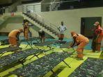 para-petugas-tengah-menyiapkan-tempat-tidur-di-gor-benhil-jakarta-pusat-pmks.jpg