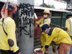 pekerja-harian-lepas-bina-marga-kecamatan-cengkareng-sedang-menghapus-coret-cat.jpg