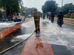petugas-pemadam-kebakaran-tengan-menyemprotkan-air-sabun-di-jalan-pemuda.jpg