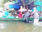 relawan-hilal-merah-indonesia-membantu-mengevakuasi-warga-yang-terjebak-banjir.jpg