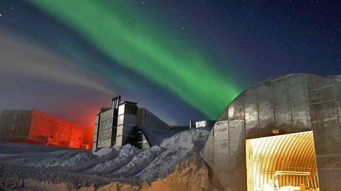 Terang bulan di Amundsen–Scott South Pole Station. Terlihat pula cahaya Aurora di langit.