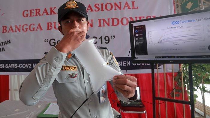 Pemeriksaan Covid-19 metode GeNose C19 menggunakan sampel udara yang dikeluarkan subjek dari mulut. Keterangan foto: Petugas Dinas Perhubungan mengembuskan nafasnya pada kantong nafas, untuk dites dengan GeNose C19 di Terminal Kampung Rambutan, Jakarta, Minggu (24/1/2021).