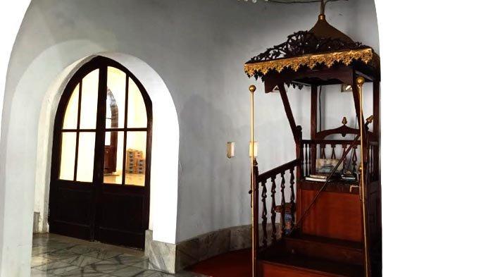 Bentuk pintu yang melengkung gaya arsitektur Islam serta mimbar bergaya Nusantara di Masjid Al-Ma'mur Cikini.
