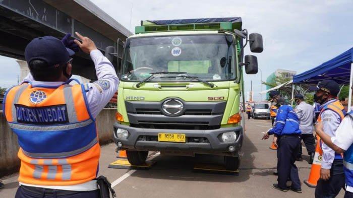 Petugas Dinas Perhubungan sedang mengarahkan truk naik ke timbangan, dalam Operasi ODOL pada Selasa (15/12/2020).
