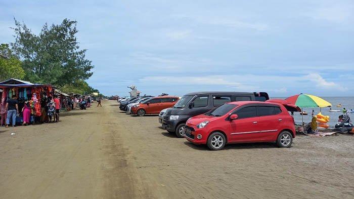 Kendaraan pengunjung Pantai Samudra Baru di Kecamatan Pedes, Karawang, memarkir mobilnya di bibir pantai, Sabtu (26/12/2020).
