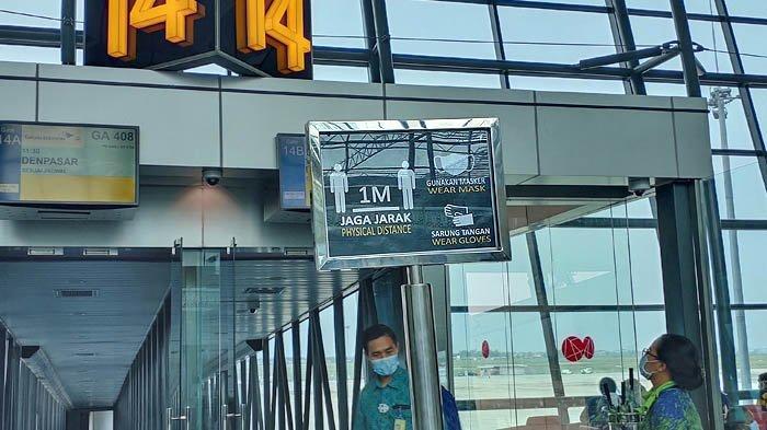 Pengumuman imbauan menjaga jarak saat naik ke pesawat.
