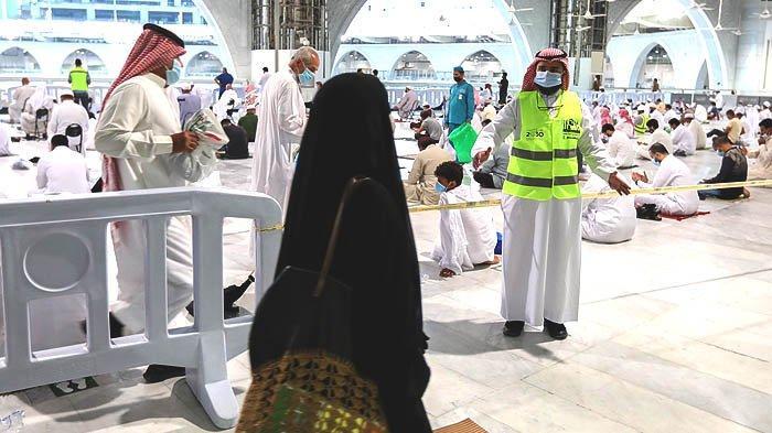 Petugas voluntir (rompi hijau) di Masjidil Haram mengarahkan jemaah. Jawatan Tinggi Pemelihara Dua Masjid Suci merekrut banyak tenaga voluntir menjelang pembukaan kembali ibadah umrah bagi jemaah internasional.