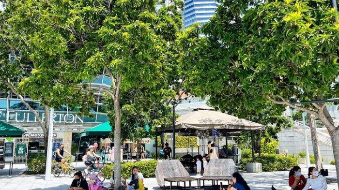 Asisten Rumah Tangga (ART) terlihat menggelar tikar berpiknik di Taman Merlion, Marina Bay dengan jumlah maksimum 2 orang pada hari pertama pemberlakuan lockdown parsial Singapura (16/5/2021).