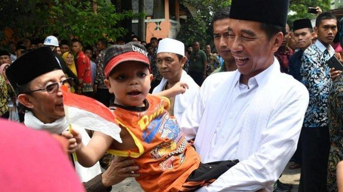 Jokowi gendong seorang anak berkebutuhan khusus di Pondok Pesantren Al-Ittihad, Cianjur, Jawa Barat, Jumat (8/2/2019).