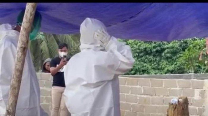 AR, anak kedua dari pasangan suami istri yang meninggal, saat mengumandangkan azan di makam ibunya