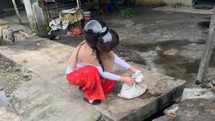 Cuplikan gambar seorang ibu melihat potongan tubuh kucing di dalam karung di di Jalan Tangguk Bongkar VII, Tegal Sari Mandala II, Kecamatan Medan Denai.