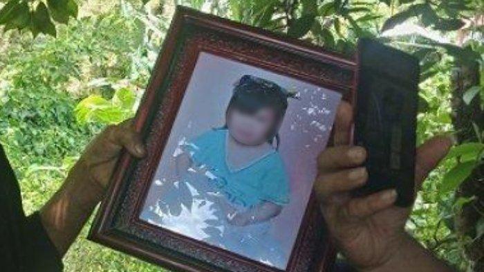 Edi Sulu Saat Memegang Foto Anaknya MS (13) yang hilang sejak Selasa (18/5/2021) dan ditemukan tewas di perkebunan pala Karumama, di Desa Koha Jaga Satu, Kecamatan Mandolang, Minahasa, Sulawesi Utara pada Kamis (20/5/2021).