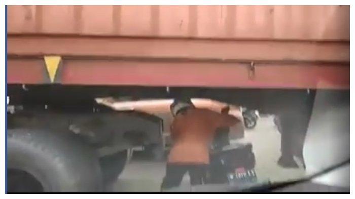 Emak-emak nekat terjanng macet dengan melewati bawa truk kontainer.