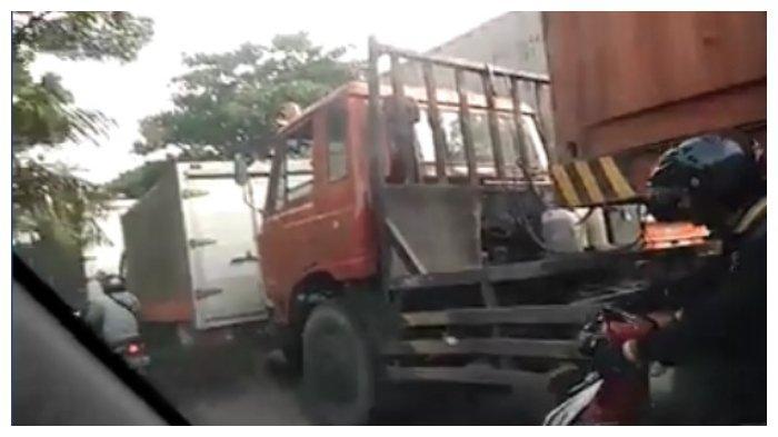 Inilah truk merah besar yang bagian bawahnya dilewati emak-emak untuk terjang kemacetan