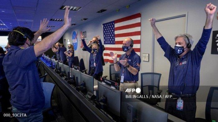 Foto NASA ini menunjukkan anggota tim penjelajah Perseverance NASA saat mereka bereaksi dalam kontrol misi setelah menerima konfirmasi bahwa pesawat luar angkasa berhasil mendarat di Mars, pada 18 Februari 2021, di Laboratorium Propulsi Jet NASA di Pasadena, California.