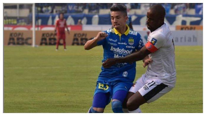 Gelandang bertahan Persib Bandung, Kim Kurniawan berduel dengan pemain Madura United, Greg Nwokolo