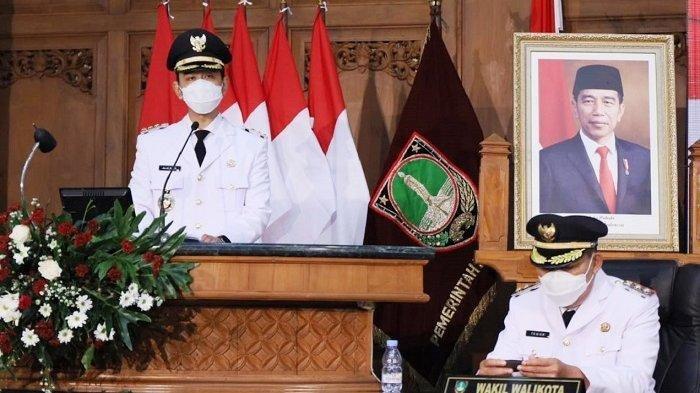 Gibran Rakabuming Raka menyampaikan pidato pertamanya menjadi Wali Kota Solo seusai pelantikan dan pengambilan sumpah dan di sampingnya foto Jokowi di Grha Paripurna DPRD Kota Solo, Jumat (26/2/2021).