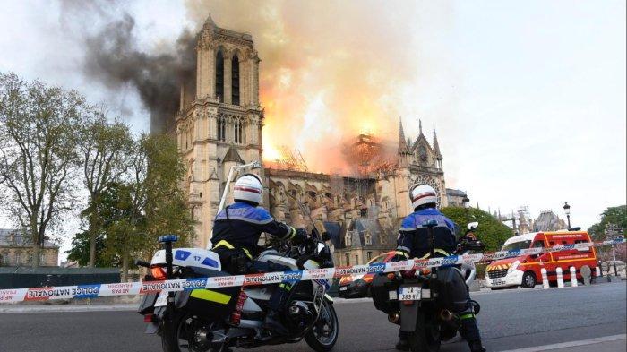 Dua orang polisi menyaksikan gereja bersejarah di dunia, Notre Dame, dilahap si jago merah.