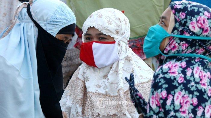 Jemaah mendengarkan khutbah seusai melaksanakan salat Idulfitri 1441 H berjamaah di halaman Masjid Nashrulloh, Kampung Bojongpeundeuy, Desa Cangkuang, Kecamatan Rancaekek, Kabupaten Bandung, Minggu (24/5/2020). Pelaksanaan salat id berjamaah ini mengenakan masker bagian dari menerapkan protokol kesehatan guna mencegah penyebaran Covid-19. (TRIBUN JABAR/GANI KURNIAWAN)