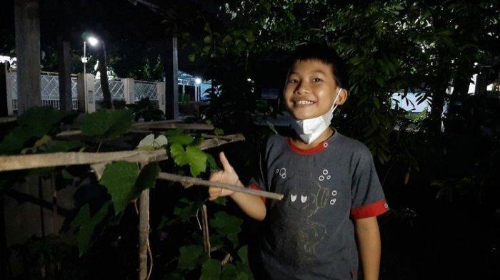 Muhammad Rizqi Maulana saat berada di depan rumahnya di Dusun Jetis, Desa Wedomartani, Kecamatan Ngemplak, Sleman. Anak SD kelas III ini viral setelah dengan sopan menulis surat untuk izin meminta buah jambu mawar kepada pemiliknya.