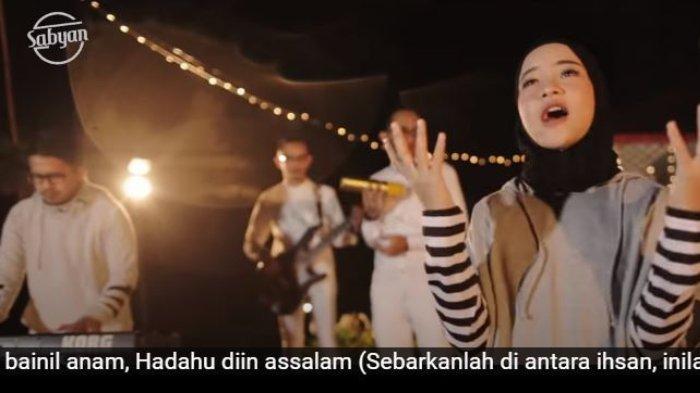 Nissa Sabyan dan Ayus memakai pakaian kembar dalam video klip Deen Assalam.