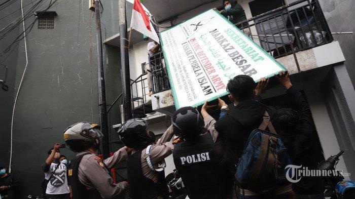 Pasukan polisi berpakaian lengkap saat menurunkan atribut Front Pembela Islam (FPI) di kawasan Petamburan, Jakarta Pusat, Rabu (30/12/2020). Sebelumnya, Menko Polhukam Mahfud MD dalam jumpa pers yang didampingi sejumlah menteri dan kepala lembaga menyatakan bahwa Pemerintah melarang aktivitas FPI dan akan menghentikan setiap kegiatan FPI, karena FPI tidak lagi memiliki legal standing. keputusan tersebut tertuang dalam Surat Keputusan Bersama (SKB) 6 Pejabat Tertinggi. Mereka yang membubuhkan teken pada SK Bersama itu adalah Menteri Dalam Negeri, Menteri Hukum dan HAM, Menteri Komunikasi dan Informatika, Jaksa Agung, Kapolri, serta Kepala Badan Nasional Penanggulangan Terorisme (BNPT).