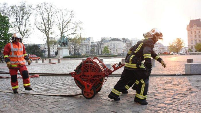 Pemadam kebakaran di Prancis yang tengah berusaha memadamkan api di Gereja Notre Dame.