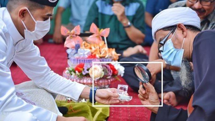 Penghulu mengecek cincin nikah pakai kaca pembesar karena disebut sebelumnya sering terjadi cincin pernikahan yang diberikan palsu.