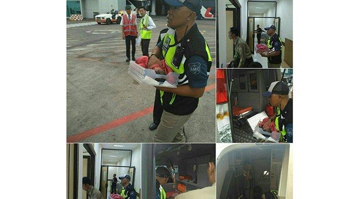 Petugas dari AMC (Apron Movement Control) Bandara I Gusti Ngurah Rai memberikan pertolongan kepada bayi yang baru lahir di dalam pesawat ke rumah sakit terdekat. Sabtu (8/7/2017)