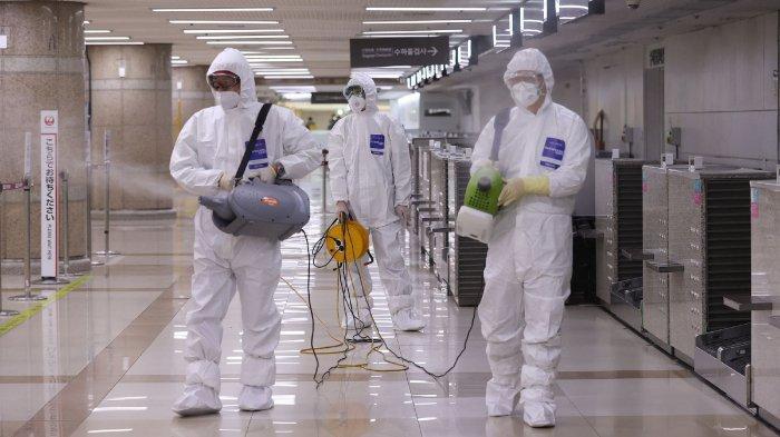Petugas menyemprotkan cairan desinfektan di Korea Selatan.