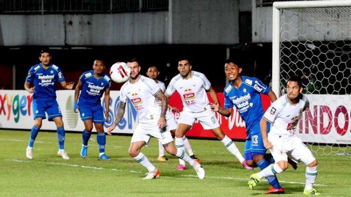Pemain PSS Sleman (putih) dan pemain Persib Bandung (biru) menanti bola di kotak penalti saat semifinal Leg pertama Piala Menpora 2021 yang berakhir dengan skor 1-2 di Stadion Maguwoharjo, Sleman, Jumat (16/04/2021) malam.