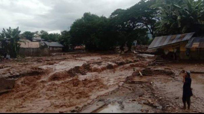 Seorang warga menyaksikan banjir bandang yang merusak permukiman di Desa Waiburak, Kecamatan Adonara Timur, Flores Timur, NTT, Minggu (04/04/2021).