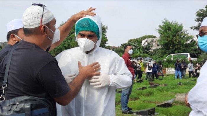 Teddy Syach saat memakai APD untuk ikut memakamkan istrinya, Rina Gunawan di TPU Tanah Kusir Jakarta Selatan, Selasa (3/3/2021).