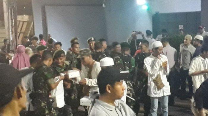 Sejumlah anggota pasukan TNI memberikan makanan kepada para demonstran yang berunjuk rasa di sekitar Kantor Bawaslu RI di Jalan MH Thamrin, Jakarta Pusat, Rabu (22/5/2019).