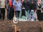 dua-perempuan-duduk-bersimpuh-di-atas-makam-terduga-teroris-yang-baru-dimakamkan_20180521_183733.jpg